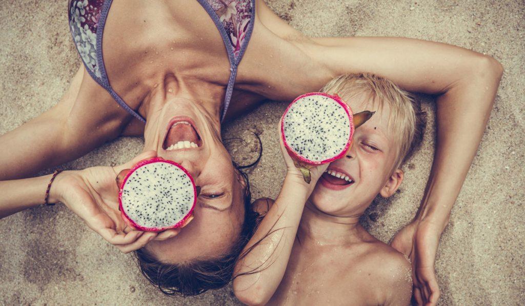 Mama und Sohn am Strand mit einer Drachenfrucht in der Hand