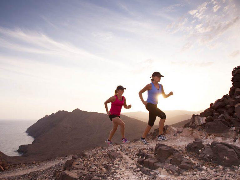 zwei Frauen rennen einen Berg rauf